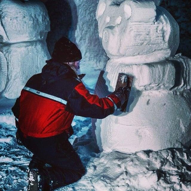 chico esculpiendo un muñeco de nieve en Laponia